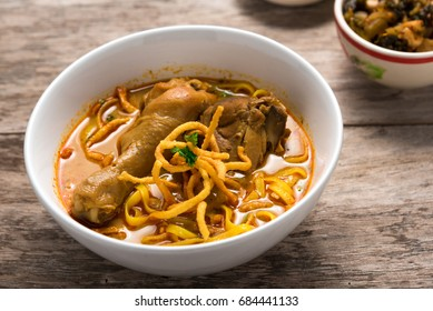 Khao Soi Recipe, Curried Noodle Soup with Chicken on wooden table,Thai food.