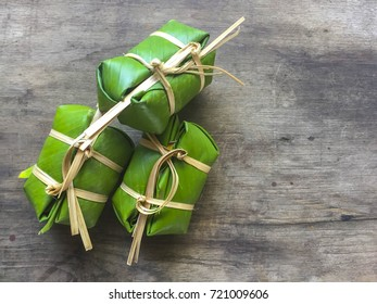 Khao Tom Mat - Thai  Sticky Rice, Banana and Black Beans Wrapped in Banana  on wooden background