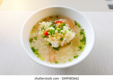 Khao Tom Seafood in Thailand, Rice boiled soup with squid and shrimp in white bowl on table.