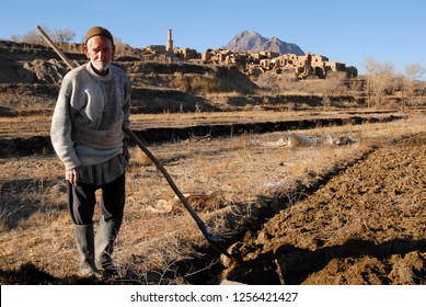 Kharanaq village, Iran - January, 2009: Authentic iranian villager (peasant) is doing his field work. Medieval adobe mud-brick village of Kharanaq.