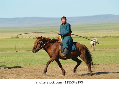KHARKHORIN, MONGOLIA - AUGUST 19, 2006: Unidentified Mongolian teenager boy wearing traditional costume rids on horse back in a steppe in Kharkhorin, Mongolia.
