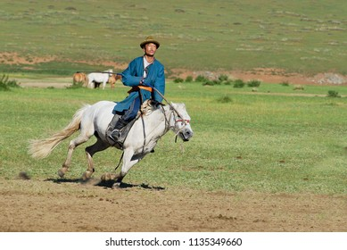 KHARKHORIN, MONGOLIA - AUGUST 19, 2006: Unidentified Mongolian man wearing traditional costume rides on horse back in a steppe in Kharkhorin, Mongolia.