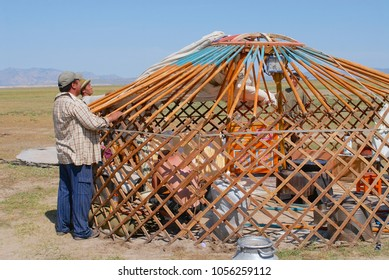KHARKHORIN, MONGOLIA - AUGUST 25, 2006: Unidentified Mongolian men assemble yurt (nomadic tent) in steppe in Kharkhorin, Mongolia. Wooden frame of a yurt is covered with pieces of felt and canvas.