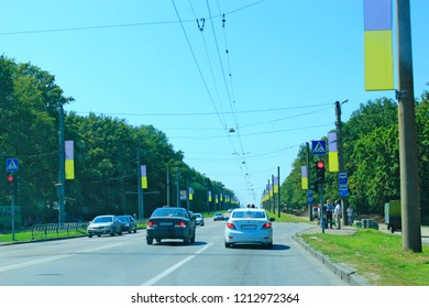 Kharkiv region Ukraine - 07 August 2016: City traffic in Kharkiv on street decorated Ukrainian national flags. Car traffic in Kharkiv. Street with moving cars. Asphalt road with dividing strip