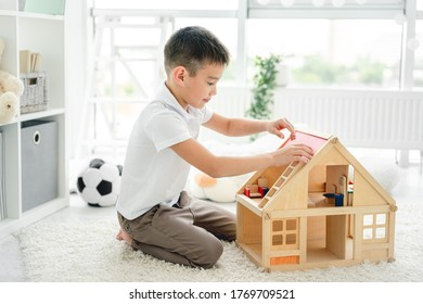 Kharkiv, Ukraine - 06 June 2020: little boy playing alone with wooden house in kids room