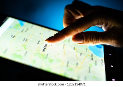 Kharkiv, Ukraine - 12 November 2018: close up girl hand using tablet with Google maps app on the screen with a dark background