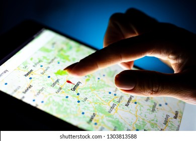 Kharkiv, Ukraine - 12 November 2018: close up girl hand using tablet with Google map app on the screen with a dark background