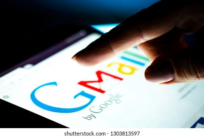 Kharkiv, Ukraine - 12 November 2018: close up girl hand using tablet with Google gmail app on the screen with a dark background