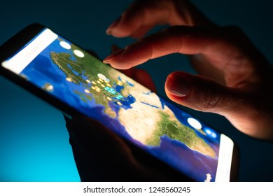 Kharkiv, Ukraine - 16 November 2018: close up girl hand using tablet with Google map app on smartphone screen with a dark background