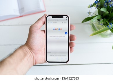 KHARKIV, UKRAINE - April 10, 2019: Man holds Apple iPhone X with Google.com site on the screen. Search page