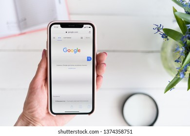 KHARKIV, UKRAINE - April 10, 2019: Woman holds Apple iPhone X with Google.com site on the screen. Search page