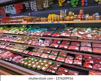 KHARKIV, UKRAINE - April 17, 2019: Large selection of meat in packs and various sauces on the shelves of the supermarket. Sale of raw meat: pork, beef, chicken, turkey. Vacuum packaging for food.