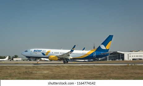 Kharkiv, Ukraine - August 19 2018: Azur Airlines plane is landing in Kharkiv airport. Plane on the runaway, ground touch. Smoke on runaway because of the ground touch. Building of the airport.