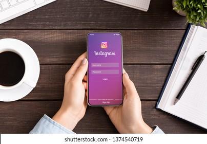 KHARKIV, UKRAINE - DECEMBER 24, 2018: Millennial woman using social media Instagram application on Apple iPhone X Max screen.