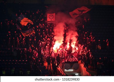 KHARKIV, UKRAINE - FEBRUARY 14, 2019: FC Shakhtar Donetsk fans and ultras using spectacular red pyro and fires on the stands. Europa League. Shakhtar Donetsk - Eintracht Frankfurt