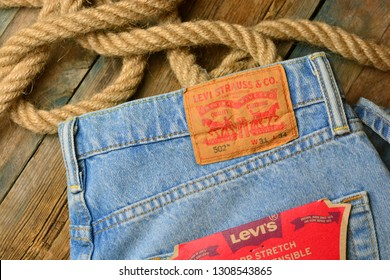 KHARKIV, UKRAINE - February 9, 2019: Legendary Levi's brand. Levis blue jeans with Levi Strauss leather tag. Denim jeans on a wooden background with rope.