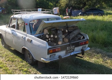 Kharkiv, Ukraine - July 08, 2019: Photo of an old car with an open trunk full of firewood for a bonfire or fireplace