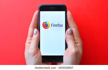 KHARKIV, UKRAINE - JULY 19, 2019: Illustrative editorial of Mozilla Firefox logo on smartphone screen in female hands.