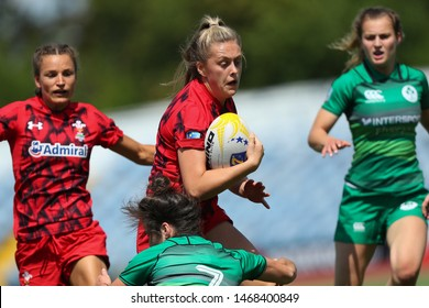 KHARKIV, UKRAINE - JULY 20, 2019: Rugby Europe Women's Sevens Grand Prix Series. Ireland-Wales. Welsh rugby player beautiful close-up portrait running fast with the ball tackled high by defender