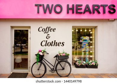 Kharkiv, Ukraine, July, 2019 Retro bicycle as a flowerbed decoration outside of coffee and clothes shop. Black aged bike stays against the wall with two garden baskets with flowers. Art decor object