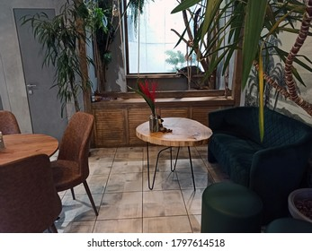 KHARKIV, UKRAINE JULY 27, 2020: Modern trendy cafe style in green and brown colors. Green plants, palms in the interior. Chairs and tables made of wood. Room design with furniture.