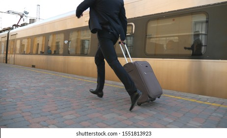 KHARKIV, UKRAINE - JULY 29, 2019: Legs of successful businessman in suit running along platform and pulling suitcase on wheels. Young confident man with his luggage missed train. Concept of business