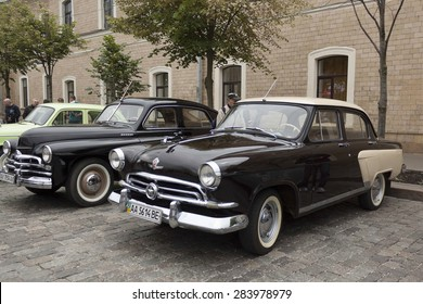 KHARKIV, UKRAINE - MAY 31, 2015: Exhibition of vintage cars on the Freedom Square in Kharkiv, May 31, 2015. In the foreground of the Soviet car Volga GAZ-21, the first industrial series 1957-1958