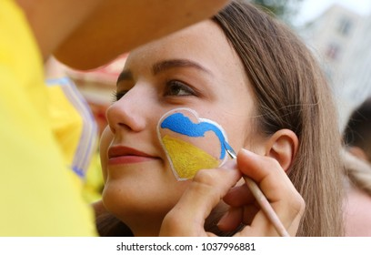 KHARKIV, UKRAINE - SEP. 2, 2017: People draw a heart on cheek during Fan-march of Ukrainian National Football Team supporters on streets of Kharkiv before World Cup 2018 qualif. game Ukraine v Turkey