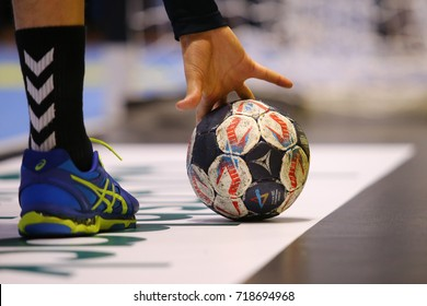 KHARKIV, UKRAINE - SEPTEMBER 14, 2017: Select official tournament match ball on the floor. Unrecognized player takes it with hand. EHF Men's Champions League. HC Motor - Chekhovskie Medvedi