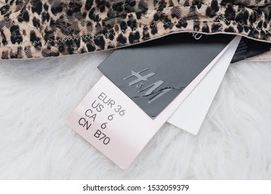 KHARKIV, UKRAINE - September 19, 2019: Label sizes and inscription H&M on the white fur. Thing with leopard print. Fashion concept
