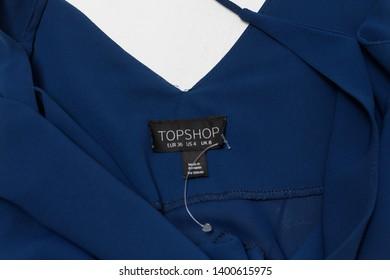 KHARKOV, UKRAINE - APRIL 27, 2019: Black TOPSHOP tag on a blue blouse. Close-up