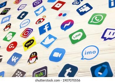KHARKOV, UKRAINE - DECEMBER 26, 2020: Paper logos of most popular social networks and mobile messengers on wooden background. Facebook instagram youtube twitter tiktok twitch reddit and others