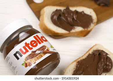 KHARKOV, UKRAINE - DECEMBER 27, 2020: Nutella glass can and spread on freshly baked bread. Nutella is manufactured by the Italian company Ferrero first introduced in 1964