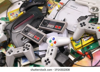 KHARKOV, UKRAINE - DECEMBER 27, 2020: Pile of old 8-bit video game consoles and many gaming accessories like a joysticks and cartridges. Old school retro gaming