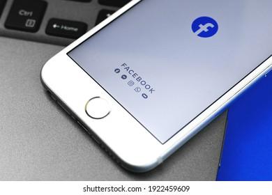 Kharkov, Ukraine - February 22, 2021: Facebook app on Apple iPhone screen, background of keyboard, photo
