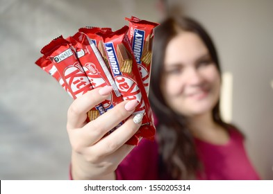 KHARKOV, UKRAINE - OCTOBER 21, 2019: A young caucasian brunette girl shows many kit kat chocolate bars in red wrapping in light room. Kit Kat chocolate manufactured by Nestle