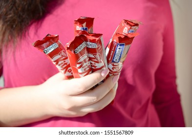 KHARKOV, UKRAINE - OCTOBER 21, 2019: A young caucasian brunette girl holds many kit kat chocolate bars in red wrapping in light room. Kit Kat chocolate manufactured by Nestle