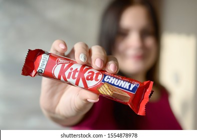 KHARKOV, UKRAINE - OCTOBER 21, 2019: A young caucasian brunette girl shows kit kat chocolate bar in red wrapping in light room. Kit Kat chocolate goods manufactured by Nestle