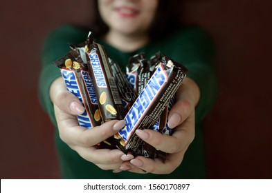 KHARKOV, UKRAINE - OCTOBER 8, 2019: A young caucasian brunette girl shows many Snickers chocolate bars in dark room. Snickers chocolate manufactured by Mars