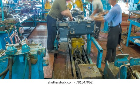 KHARKOV, UKRAINE - SEPTEMBER 2016: Tractor engine assembled on the factory production line on tractor factory timelapse. Workers in uniform install gear parts
