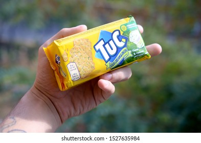 KHARKOV, UKRAINE - SEPTEMBER 23, 2019: Tuc snack pack in male hand on a green trees background. TUC is a brand of snack biscuit marketed by Mondelez International