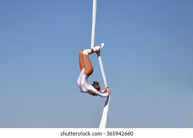 Kharkov, Ukraine - September 27, 2015: Feldman Ecopark in Kharkov on September 27, 2015. Show of trapeze artists. Young woman gymnast. On sky background. Trapeze artist in the sky.