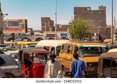 Khartoum, Sudan, February 5. 2019: Street scene with pedestrians, cars, a yellow van and a red Tuc-Tuc in front of a market place in Omduram