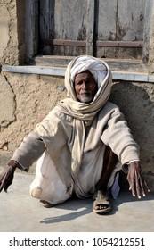 Khempur, Rajasthan, India, December 24, 2014. Turbanned Old Man in Rags Squatting outside his Home in Khempur, Rural Rajasthan, India