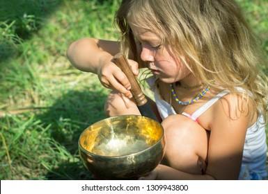 Kherson. Ukraine - August 20, 2018: Little girl explores meditative instrument - trying play instrument. Tibetan bowls