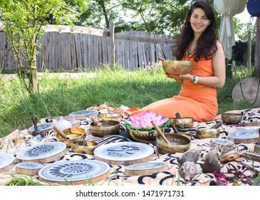 KHERSON, UKRAINE - July 18, 2018: Spiritual festival of meditative music. Happy girl shows a musical healing collection of instruments with a harmonizing calming effect outdoors. Sound therapy