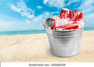 KHERSON, UKRAINE - JUNE 24, 2019: Three Coca-Cola cans in an ice bucket. Coke is one of the most popular soft drinks in the world.