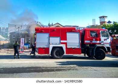 KHERSON, UKRAINE - JUNE 8, 2019: Fire engine KAMAZ and firefighters on fire in cafe