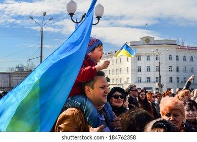 KHERSON, UKRAINE - MARCH 30, 2014: patriotic demonstrators of all ages at the meeting for integrity of democratic Ukraine against Russian intervention with national symbols.