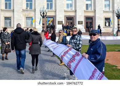 KHERSON, UKRAINE - MARCH 30, 2014: people unfold extremely long Ukrainian traditional embroidered by hand towel to integrity of Ukraine and to 70th jubilee of institution of Kherson region.